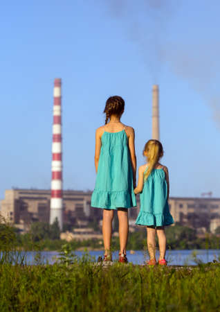 care future concept. sisters are looking at the chimney-stalks polluting an air