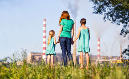 polluting: care future concept. Young mother with her kids are looking at the chimney-stalks polluting an air Stock Photo