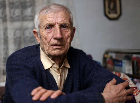 un homme triste: portrait d'homme �g� assis � la maison