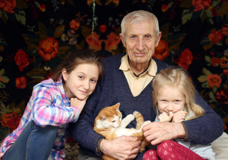 grandkid: portrait of  sitting senior man and  granddaughters at home Stock Photo