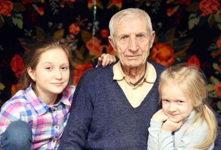 granddaughters: portrait of  sitting senior man and  granddaughters at home Stock Photo