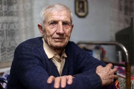 hombre solitario: retrato de hombre sentado senior en casa