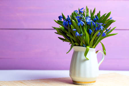 snowdrops in a vase on a table on a pink background