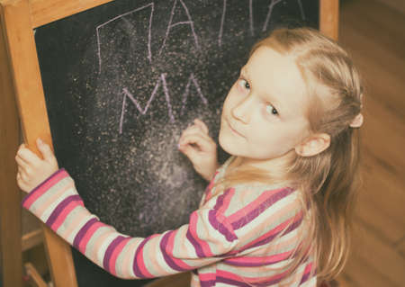 Girl draws on an easel  in the nursery photo