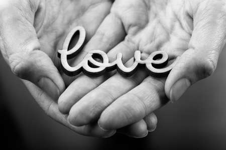 hands holding word love  black on white photo