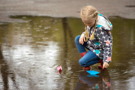 Girl runs the pink paper boat in a puddle in the rain photo