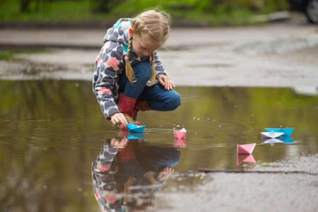 Girl runs the pink paper boat in a puddle in the rain, spring photo