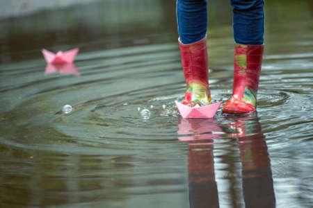 rain boots: Ni�a corre el barco de papel de color rosa en un charco en la lluvia, la primavera