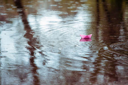 Pink paper boat in a puddle in the rain photo