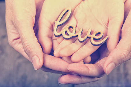 retro vintage: hands holding word love Stock Photo