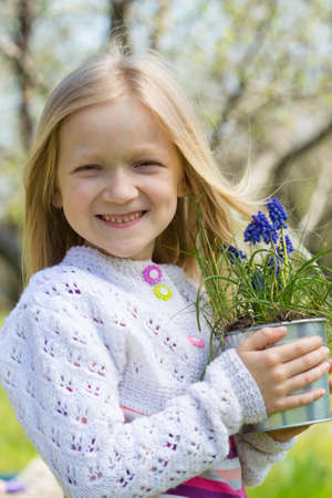 hyacinths: smiling girl holding flowers hyacinths  in a pot