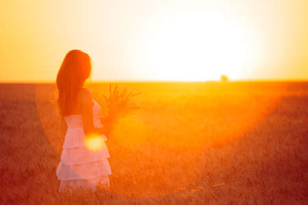 joy: young girl joys on the wheat field at the sunset time