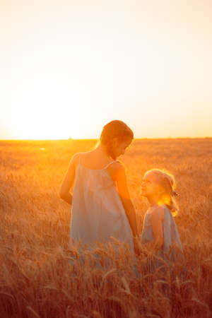 joys: young girls joys on the wheat field  at the sunset time