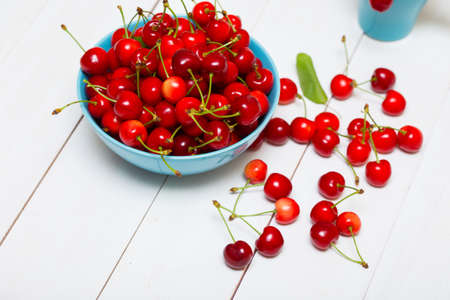 cherry: red cherries in a beautiful blue bowl on a white wooden background
