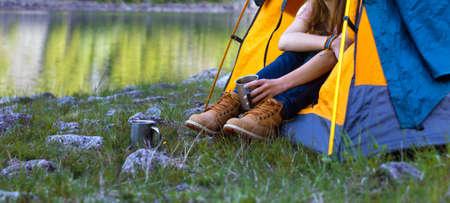 fille randonneur dans une tente et tenant une tasse montagnes en arrière-plan