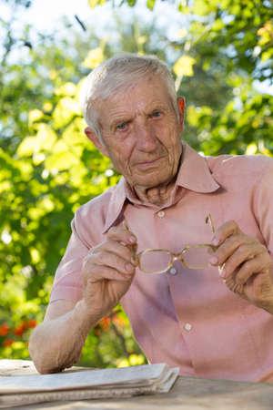 homme triste: Portrait d'un homme �g� assis � une table dans le jardin