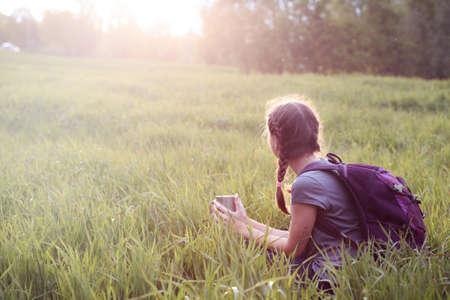 meadow  grass: Muchacha del caminante sentado en una pradera de c�sped y disfrutar de una puesta de sol Foto de archivo