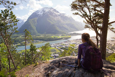 trekking pole: girl hiker with a backpack and trekking pole sitting and looking on Romsdalsfjorden and Andalsnes, Norway