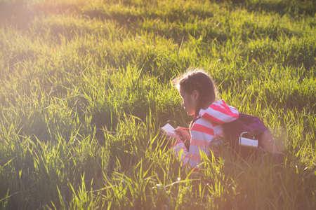 meadow  grass: girl hiker sitting on a meadow grass and enjoying a sunset