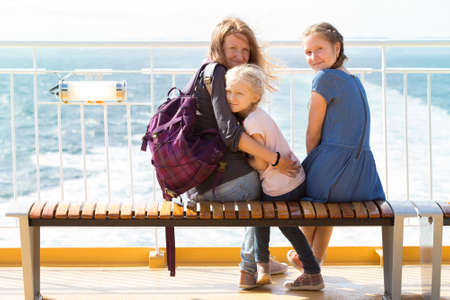 mother on bench: family - mother and two daughters sitting on a bench on the ferry and the sea in the background
