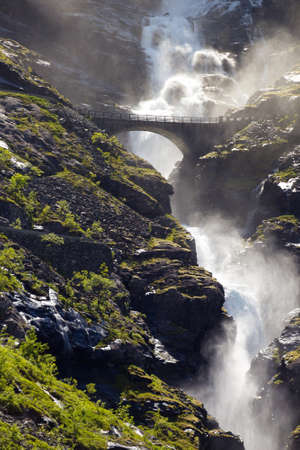 range of motion: arch bridge and waterfall on the road Trollstigeveien - meandering road at the norwegian mountains, Norway Stock Photo