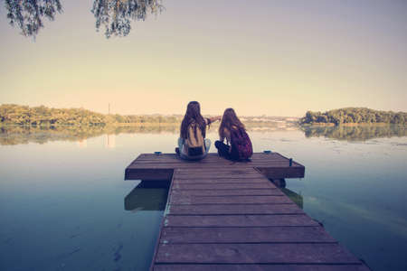 river bank: Two teenager girls with backpacks sitting on a pier at the river bank and the city in the background