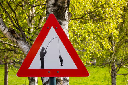 carefully: road sign - carefully fisherman catches a fish, norway Stock Photo