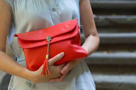 clutch: girl holding a beautiful red clutch outdoors