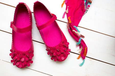 pink shoes: Childrens bright pink shoes on a  wooden background