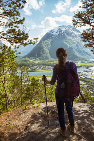 trekking pole: Rampestreken. girl hiker with a backpack and trekking pole standing and looking on Romsdalsfjorden and Andalsnes, Norway