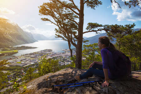 trekking pole: Rampestreken. girl hiker with a backpack and trekking pole sitting and looking on Romsdalsfjorden and Andalsnes, Norway