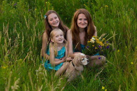 mother and two smiling daughters sitting on the grass at the evening field photo