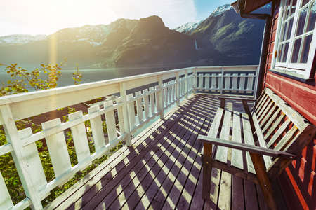 terrace house: benches for rest at the norwegian terrace house with mountains and a waterfall in the background, norway