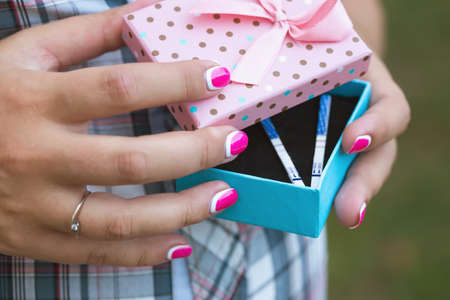 test results: Beautiful female hands hold the box in which lie pregnancy tests Stock Photo