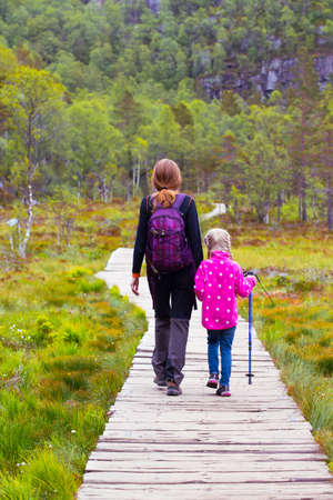 in the woods: hikers mom and daughter walk along the trail through the woods on  Preikestolen, norway