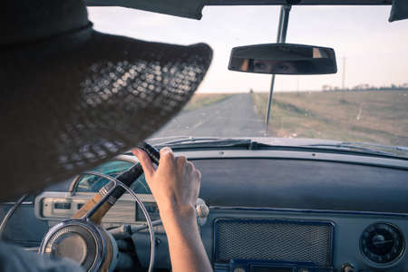 young girl driving a retro car by the road at the fields photo