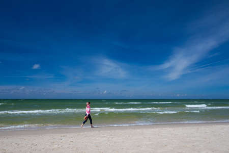 windy: girl walking along an empty beach at sunny windy day