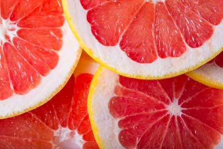 nature pattern: background made with a heap of sliced grapefruits Stock Photo
