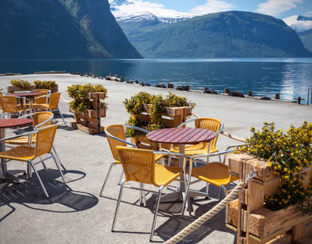europe travel: cafe. tables and chairs on the shore of the fjord in Norway