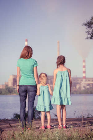 soil pollution: care future concept. Young mother with her kids are looking at the chimney-stalks polluting an air Stock Photo