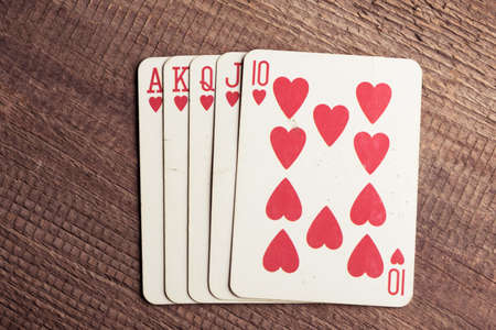 flush: flush royal combination cards lying on a wooden table
