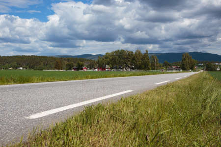 blue sky and fields: empty country road with the houses on a hills at Norway