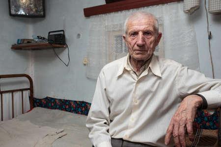 senior man sitting at his rural house