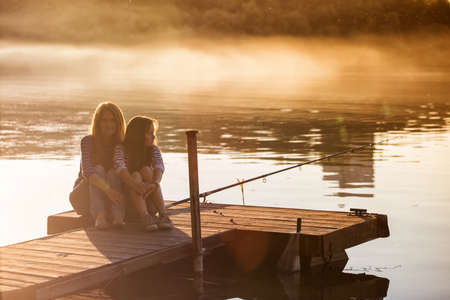 Mama with teen daughter sitting on the banks of the Dnieper River Reklamní fotografie