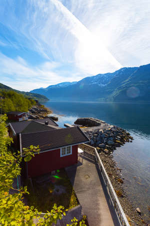 rorbuer: rorbuer - traditional norwegian red wooden house to stand at the lakeside and mountains in the distance, norway Stock Photo