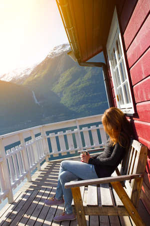 rorbu: girl sitting near rorbu and admires the beautiful Norwegian landscape at the fjord and mountains Stock Photo