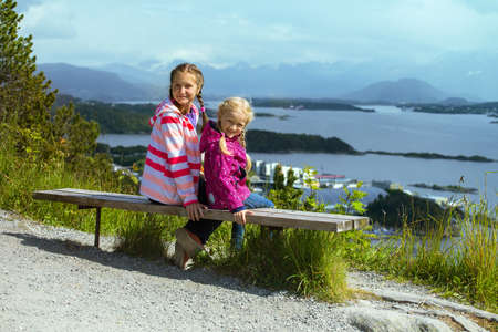 alesund: two girls sisters sitting on a bench in the town of Alesund and the mountains to the fjord in the background, norway