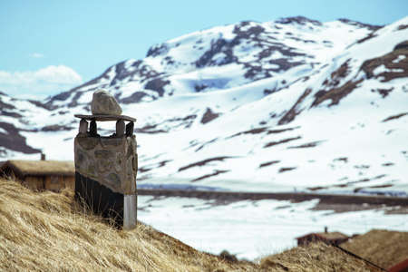 stove pipe: chimneys on the norwegian traditional house and snow capped mountains in the background