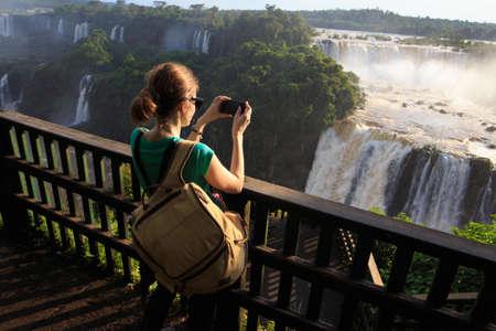 girl taking a photo of Iguassu waterfall with smartphone Stock Photo