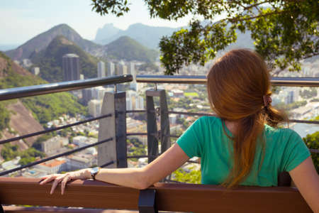 pao: girl tourist sitting and resting on the bench on the background Rio de Janeiro. view from Pao de Acucar